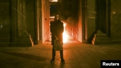 Russian artist Pyotr Pavlensky stands in front of the Federal Security Service (FSB) headquarters in central Moscow shortly after he had set fire to one of the building's doors.