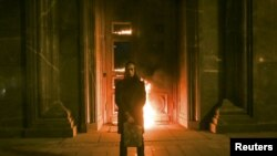 Петро Павленський перед палаючим входом у головну будівлю ФСБ Росії. Москва, 9 листопада 2015 року