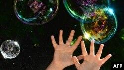 Ребенок играет с мыльными пузырями во время благотворительной акции в поддержку детей, страдающих аутизмом.