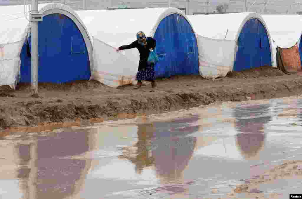 A displaced Iraqi woman who fled the Islamic State stronghold of Mosul walks following heavy rain at Khazer camp. (Reuters/Ammar Awad)