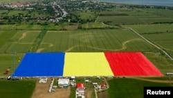 Вид с воздуха на самый большой в мире флаг, развернутый в Румынии. Окрестности Бухареста, 27 мая 2013 года.