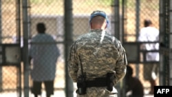 A guard watches over detainees inside the exercise yard at Camp 5 detention facility at the Guantanamo Bay prison.