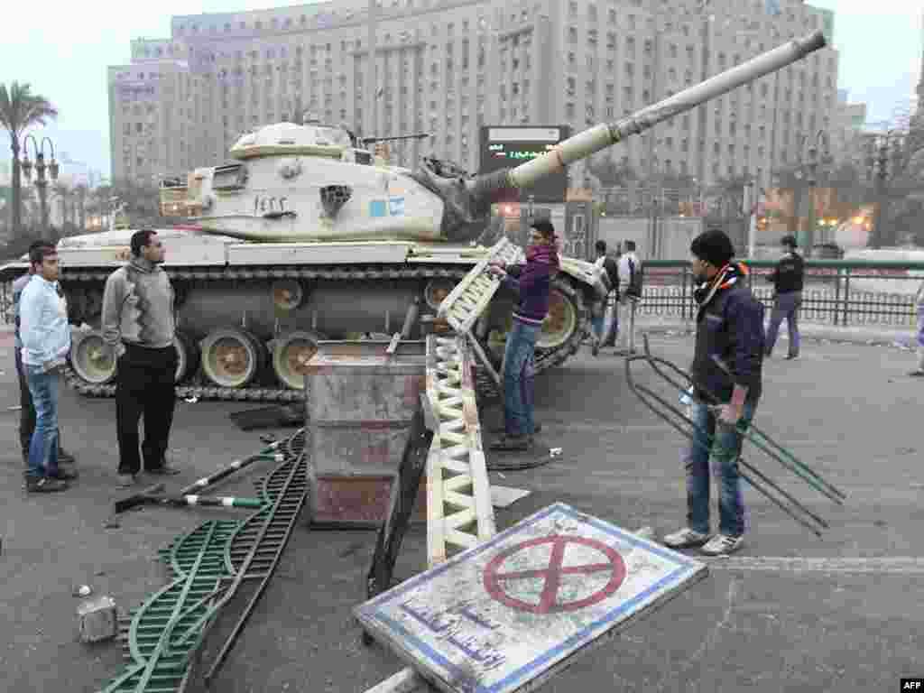A man builds a barricade in front of a tank in central Cairo on January 29.