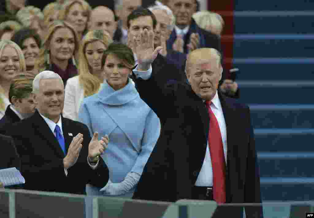 U.S. -- Vice-president elect Mike Pence (L) applauds as President-elect Donald Trump waves to the crowd as he arrives on the platform at the US Capitol in Washington, DC, on January 20, 2017,