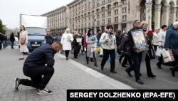 Мужчина преклонил колено перед шествием, посвященном памяти всех жертв российско-украинского конфликта. Киев, 8 мая 2019 года