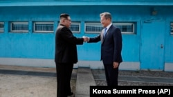 North Korean leader Kim Jong Un (left) shakes hands with South Korean President Moon Jae-in at the border village of Panmunjom in the demilitarized zone on April 27.