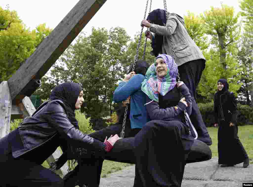Yasmin (left), 16, pushes Hana, 16, on a swing after finishing their school exams in Hackney, east London. Hana started wearing a head scarf full-time at the age of 12. She already wore it at school and her family supported her choice. She says she felt that nothing changed with the decision -- except her relationship with God.