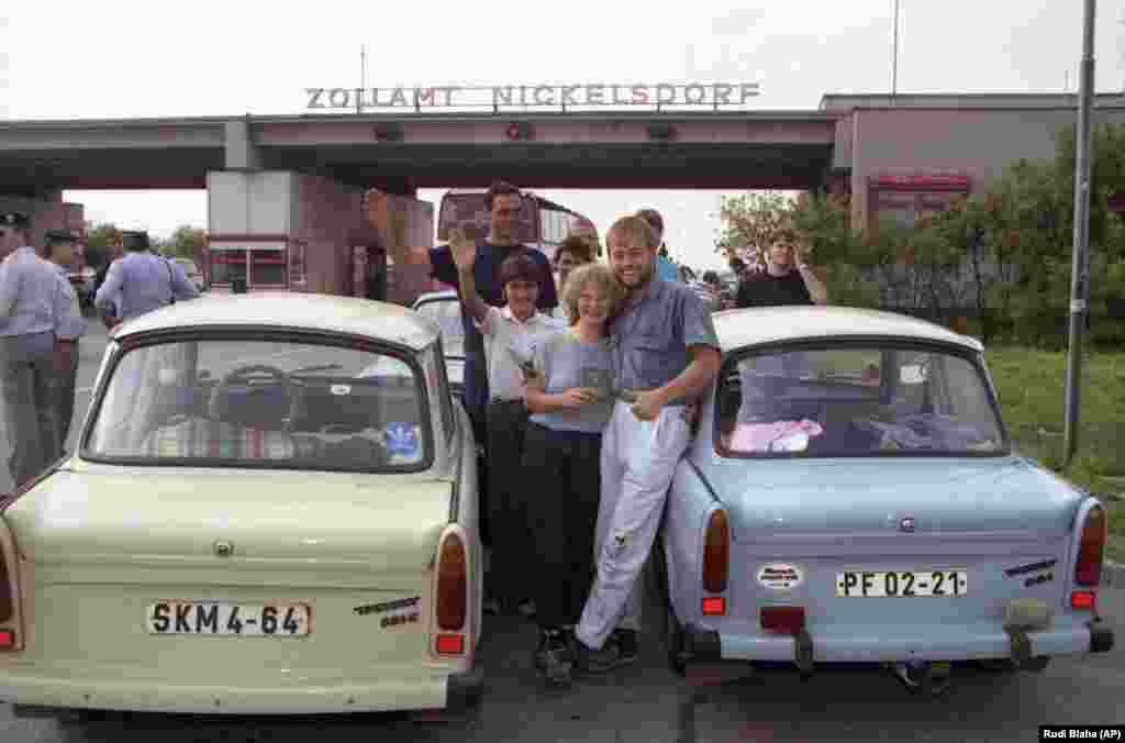 East Germans refugees smile next to their Trabants after crossing into Nickelsdorf, Austria.