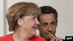 German Chancellor Angela Merkel and French President Nicolas Sarkozy arrive to address a news conference at the Chancellery in Berlin on June 17.