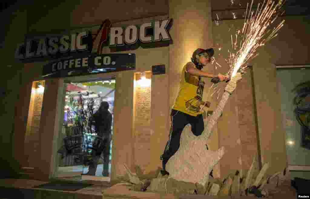 Afridi uses a circular saw as she sculpts a stone guitar outside Classic Rock Coffee.