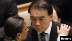 China's Ambassador to the UN, Li Baodong, speaks with U.S. envoy Susan Rice at a Security Council meeting on March 17.