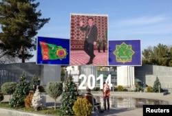 Люди сидят рядом с украшенными елками на фоне портрета президента Туркменистана Гурбангулы Бердымухамедова. Ашгабат, 13 декабря 2013 года.