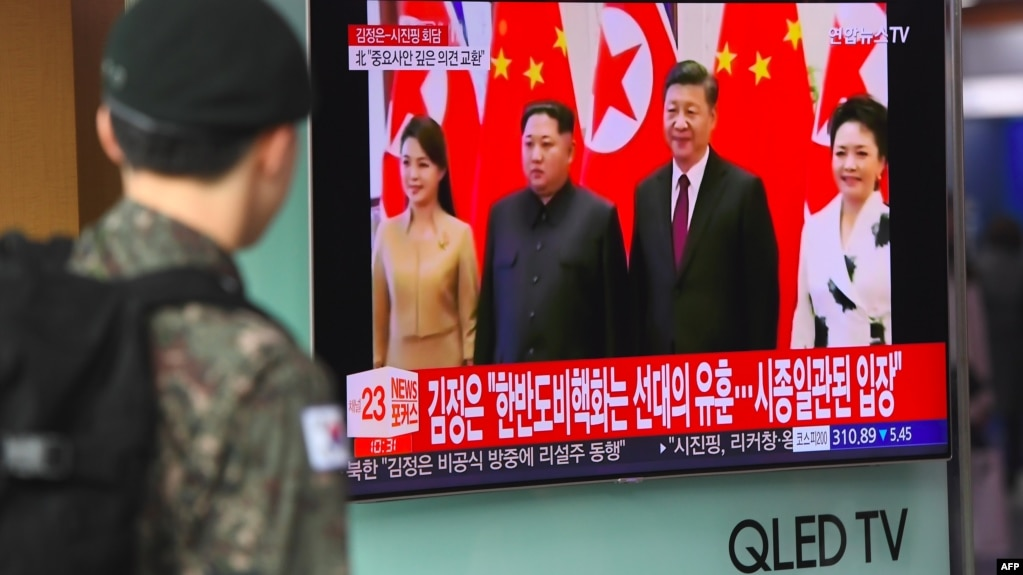 Оңтүстік Корея сарбазы теледидардан Солтүстік Корея басшысы Ким Чен Ынның Қытай төрағасы Си Цзиньпинмен кездесуі жайлы хабарды көріп тұр. Сеул, 28 наурыз 2018 жыл.