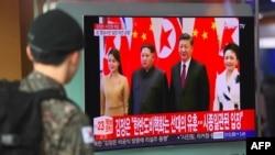 Військовослужбовець Південної Кореї на залізничній станції у Сеулі спостерігає з екрану повідомлення про візит лідера КНДР до Китаю, 28 березня 2018 року