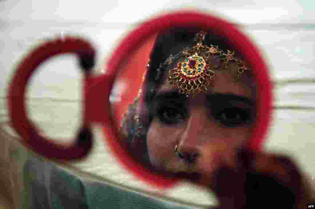 A Pakistani bride looks in a mirror as she attends a mass wedding ceremony in Karachi. (AFP/Asif Hassan)
