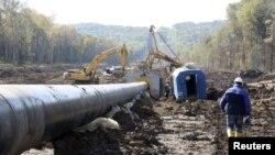 Рабочий идет вдоль строящегося нефтепровода. Иллюстративное фото.