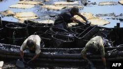 Далянь қаласы маңында суға төгілген мұнайды жинап жүрген қытай жұмысшылары. Ляонин провинциясы, 27 шілде 2010 ж.