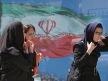 Iran --  Iranian women pass a billboard of Iran's national flag at a street in Tehran, 23Apr2007