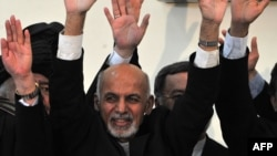 Afghan president-elect Ashraf Ghani gestures with officials during an event at the Independent Electoral Commission (IEC) office in Kabul on September 26, 2014.