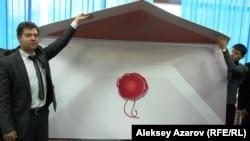 Молодежные активисты демонстрируют гигантский конверт размером полтора на два метра, в котором отправляют поздравления Нурсултану Назарбаеву. Алматы, 29 ноября 2012 года.