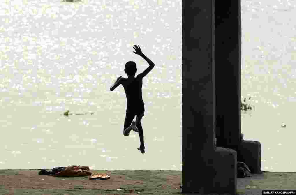An Indian youth leaps into the flooded Ganges River in the Jushi area of Allahabad. (AFP/Sanjay Kanojia)