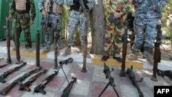 جنود عراقيون يعرضون أسلحة لعناصر جماعات مسلحة
