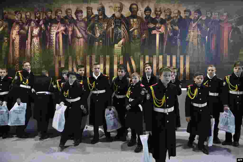 Military cadets gather in front of a huge poster depicting members of the Rurik dynasty during a mass lesson at Moscow's VDNH exhibition center. (AFP/Natalia Kolesnikova)