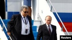 Посол России в Турции Андрей Карлов (слева) и президент России Владимир Путин в международном аэропорту Стамбула. 10 октября 2016 года.