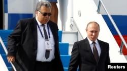 Ресей президенті Владимир Путин мен Ресейдің Түркиядағы елшісі Андрей Карлов Стамбул әуежайында. 10 қазан 2016 жыл.
