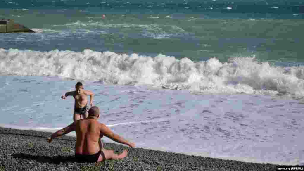На берегу дети и взрослые продолжают наслаждаться солнцем