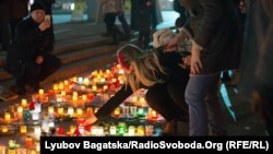 A woman in Kyiv adds a candle to an impromptu memorial for the victims of rocket attacks on Mariupol, which killed dozens of people on January 24.