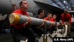 Militari transportînd o rachetă la bordul purtătorului de avioane american USS Abraham Lincoln în Golful Persic, 10 mai 2019