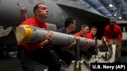Aviation Ordnancemen transport a missile aboard the Nimitz-class aircraft carrier USS Abraham Lincoln in the Persian Gulf, May 10, 2019