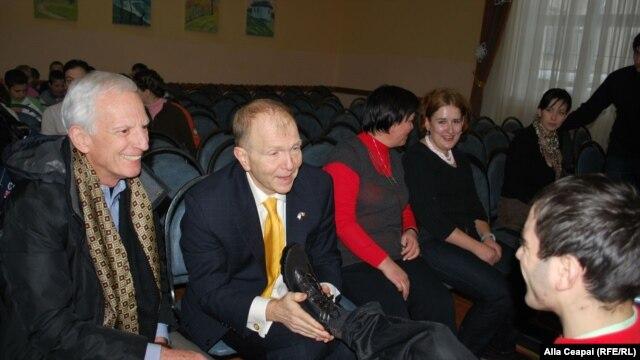 Ambasadorul american William H. Moser încălțînd copii la Școala internat nr. 5 din Chişinău.