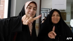 Iranian women display their ink-stained fingers after casting their ballot for the second round of parliamentary elections at a polling station in Robat Karim, some 40 kilometers southwest of the capital, Tehran.