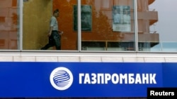 Russia -- A person is pictured through a window above a Gazprombank branch in Moscow July 17, 2014.