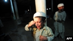 A young student cries after being rescued following a police raid on a madrasah in Karachi on December 12.