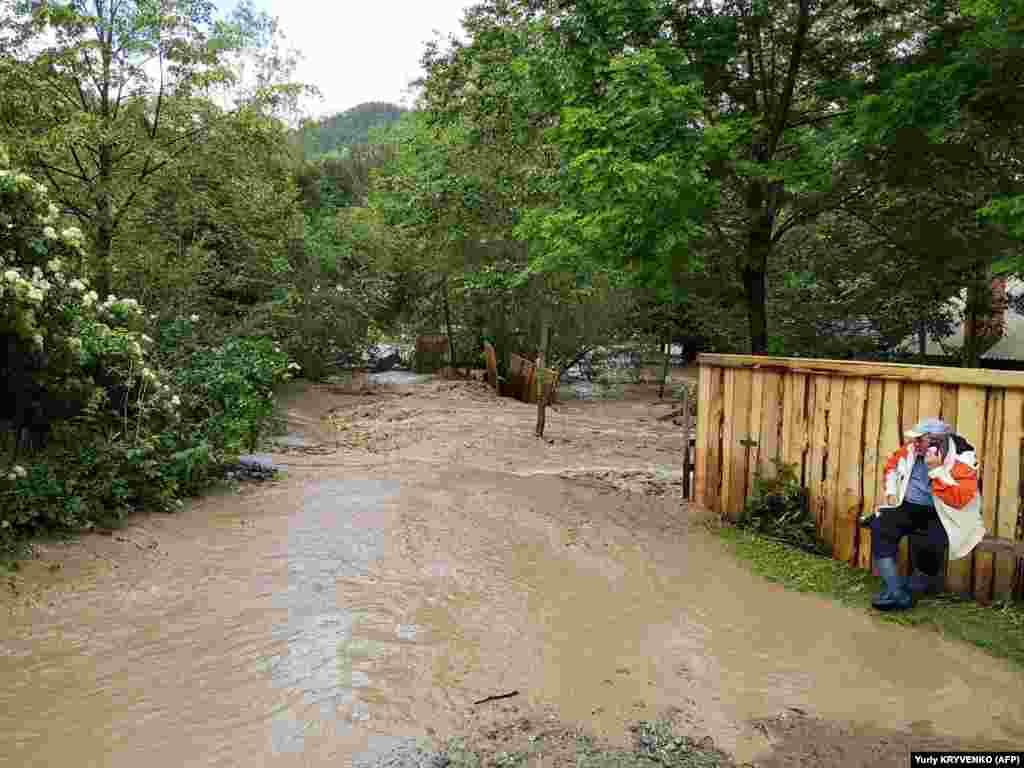 Чоловік розмовляє по телефону в затопленому селі Криворівня (Івано-Франківська область), 23 червня