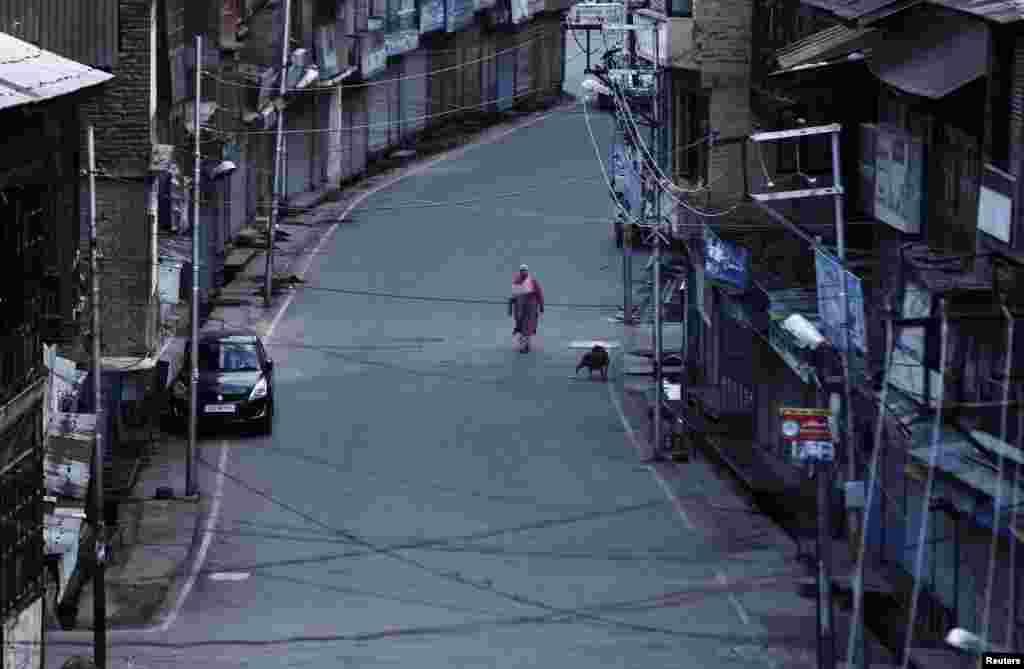 Një grua ecë nëpër rrugët e boshatisura të Kashmirit.India, pas revokimit të autonomisë ka vendosur masa të rrepta sigurie dhe kufizime të lëvizjeve.