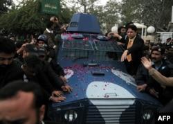 Пенджаб губернаторы Салман Тасирді атып өлтірген күзетші Малик Мумтаз Хусеин Қадриді тиеген полиция көлігін қаумалай қоршаған жұрт. Равалпинди, 6 қаңтар 2011 жыл