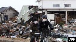 Stanovnici voze bicikle u gradu Sendaj u prefakturi Mijagi nakon udara cunamija, 21. mart 2011.