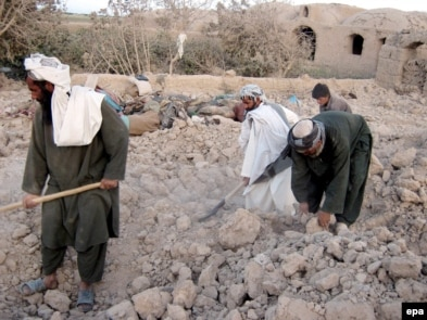 Men in the village in Farah Province search for their belongings after a U.S.-led air strike.