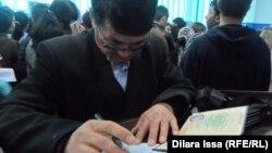 Мужчина заполняет документы на ярмарке вакансий в Шымкенте. 18 апреля 2015 года.