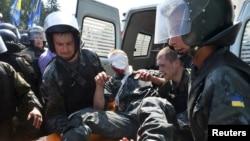 Ұлттық гвардия сарбаздары жараланған сарбазды көлікке отырғызып жатыр. Киев, Украина, 31 тамыз 2015 жыл.