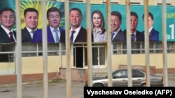 A car drives past a campaign banner in the village of Arashan, some 20 kilometers from Bishkek, on September 30.