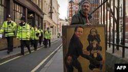 Человек с сатирическим портретом британского премьер-министра Дэвида Кэмерона ждет его прибытия в суд. Лондон, 14 июня 2012 года.