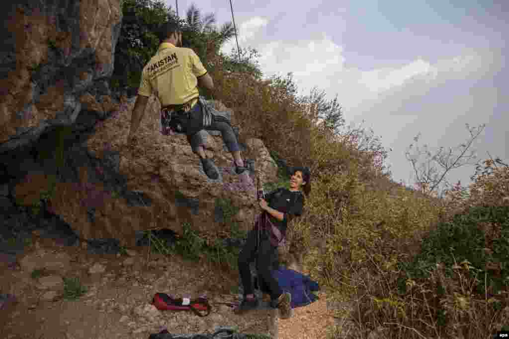 Rock climber Nazia Parveen (right) jokes with her trainer Imran Junaidi in Islamabad. Parveen, who comes from Pakistan's Federally Administered Tribal Areas, says she wants to change the image of women in her home region. She says that nothing is impossible for a woman who is focused on her goals.