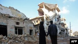 Подружжя жителів Алеппо біля зруйнованого будинку у північно-східному районі Хайдарії, грудень 2016 року