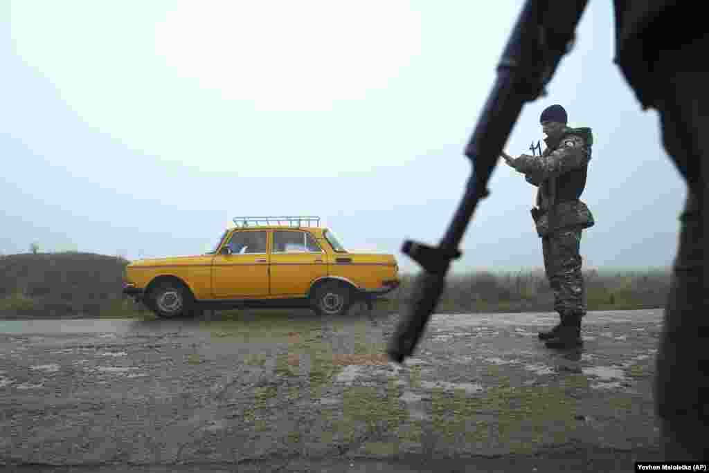 A car is stopped by Ukrainian police officers at a checkpoint in Berdyansk on the south coast of the Sea of Azov on November 27. Tensions between Kyiv and Moscow escalated after Russian border guards opened fire and captured three Ukrainian naval vessels and 24 seamen on November 25 off the coast of Crimea, which Russia forcibly annexed from Ukraine in 2014. (AP/Evgeniy Maloletka)