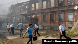 Police officers and municipal workers run with a hose as they attempt to extinguish a fire in Rostov-on-Don on August 21.